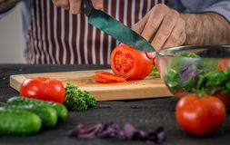 Male hands cutting vegetables for salad. Close up on male hands cutting tomato, making salad. Chief cutting vegetables. Healthy lifestyle, diet food Stock Photos