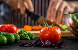 Male hands cutting vegetables for salad. Close up tomato, making salad. Chief cutting vegetables. Healthy lifestyle, diet food Royalty Free Stock Image