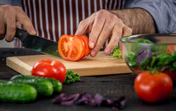 Male hands cutting vegetables for salad. Close up on male hands cutting tomato, making salad. Chief cutting vegetables. Healthy lifestyle, diet food Stock Images