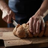 Male hands cutting wheaten bread, closeup. Male hands cutting wheaten bread on the wooden board. Close up. The healthy eating and traditional bakery concept royalty free stock images