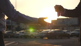Male hands of dealer giving keys of car to client with sun flare at background. Arm of businessman passed car key. Handshake between two business men outdoor stock video footage