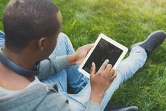 Male hands with digital tablet closeup,over shoulder shot outdoors. Male hands with digital tablet closeup, over shoulder shot. African-american student working Stock Images
