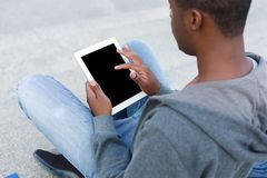 Male hands with digital tablet closeup,over shoulder shot outdoors. Male hands with digital tablet closeup, over shoulder shot. African-american student working Royalty Free Stock Photography