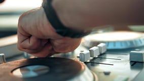 Male hands of Disk Jockey mixing music tracks tweak various controls on deck stock video footage