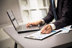 Male hands doing paperwork with pen and laptop. Stock Photos