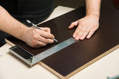 Male hands draw a pencil on the ruler. Men`s hands draw a pencil on the ruler with a sub-standard template for cutting out furniture details Royalty Free Stock Images