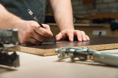 Male hands draw a pencil on the ruler. Men`s hands draw a pencil on the ruler with a sub-standard template for cutting out furniture details next to the jigsaw Royalty Free Stock Image
