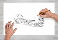 Male hands drawing a self-balancing board on white paper with a pencil in close view. royalty free stock photo