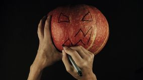 Male hands draws scary face jack o lantern on a pumpkin black surface POV stock video footage