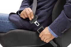 Male hands fastening a car seat belt for road safety. Isolated on white background royalty free stock images