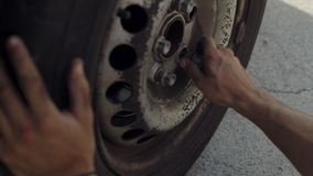 Male hands fixing flat tire of car. Close focus on dirty mechanics hands screwing big wheel bolts while changing flat tire on van stock video footage