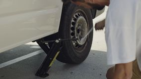 Male hands fixing flat tire of car. Unrecognizable man uses tire jack to lift up his van to change flat tire. Occasional accident on summer adventure trip stock footage
