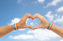Male hands with gay pride wristbands showing heart stock images