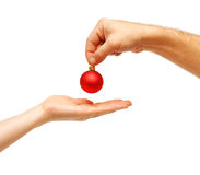 Male hands give a christmas ball to female hands Stock Images