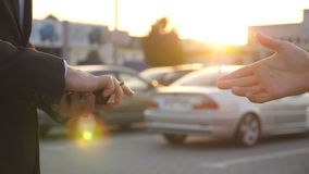 Male hands giving keys of car to his friend with sun flare at background. Arm of businessman passed car key. Handshake. Between two business men outdoor. Close stock video