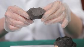 Male hands in gloves holding coal. Scientist with a sample of coal. Black coal in miner`s hand Royalty Free Stock Image