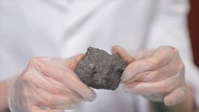 Male hands in gloves holding coal. Scientist with a sample of coal. Black coal in miner`s hand Stock Photo
