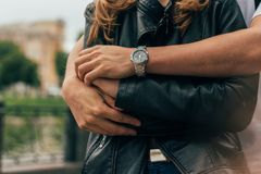 The guy is behind and hugs the girl, hands together.on the hand of a guy wearing watch.date.male hands, hands close-up, embrace an stock images
