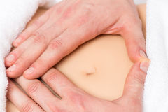 Male hands in a heart shape on the abdomen of a pregnant woman. Male hands in a heart shape on the abdomen of a pregnant women close-up stock photography