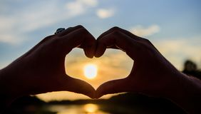 Male hands in heart shape gesture symbol of love and romance. Heart gesture in front of sunset above river water surface. Defocused. Top places for romantic royalty free stock image