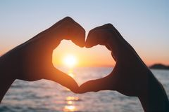 Male hands in a heart shape. At sunset Stock Photo