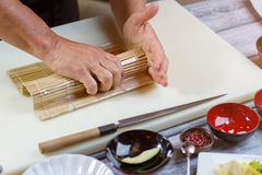 Male hands hold bamboo mat. Royalty Free Stock Images