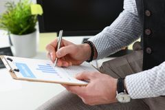 Male hands hold clipboard pad financial statistics. Male hands hold clipboard pad with financial statistics at office workspace closeup. White collar check money Stock Photos