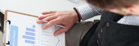 Male hands hold clipboard pad financial statistics. Male hands hold clipboard pad with financial statistics at office workspace closeup. White collar check money Stock Images