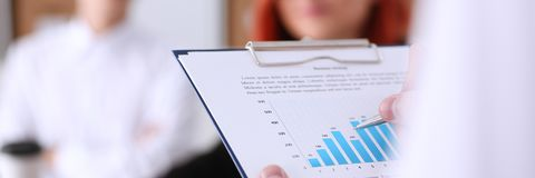 Male hands hold clipboard pad with statistics. Male hands hold clipboard pad with financial statistics at office workspace closeup. White collar check money Stock Photography