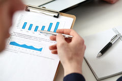 Male hands hold clipboard pad with financial statistics. At office workspace closeup. White collar check money papers, stock exchange market, internal Revenue Royalty Free Stock Photo