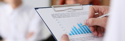 Male hands hold clipboard pad with statistics. Male hands hold clipboard pad with financial statistics at office workspace closeup. White collar check money Stock Image