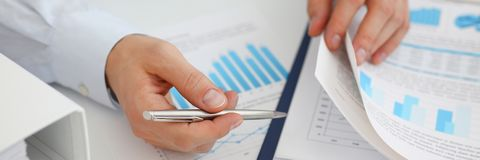 Male hands hold documents with financial statistic. S at office workspace closeup. White collar check money papers stock exchange market internal Revenue Service Royalty Free Stock Photography