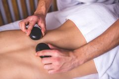 Male hands hold hot stones on the female back. The lower part of the body is covered with a white towel. Stone therapy Royalty Free Stock Photo