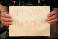 Male hands the poster with an inscription: no war on Syria. Male hands hold the poster with an inscription : no war on Syria royalty free stock image