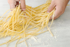 Male hands hold raw homemade noodles on white background. Men`s hands hold a raw homemade noodles on a white background close up Stock Photography