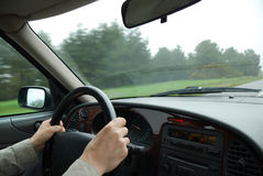 Male hands hold steering wheel. Car interior inside, landscape running through windshield Stock Photo