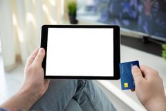Male hands holding bank card and computer tablet  screen. Male hands holding bank card and computer tablet with  screen in the house in the room stock photos