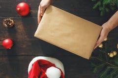 Male hands holding big box christmas present table top view background. Male hands holding big box christmas present on wooden table top view. Rustic Christmas stock images