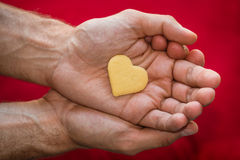 Male hands holding biscuit heart Stock Photo