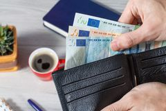 Male hands holding black leather wallet full of euro bills on gr. Male hands holding black leather wallet full of euro bills. Cup of coffee, notebook, pen and Royalty Free Stock Photography