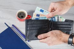 Male hands holding black leather wallet full of euro bills on gr. Male hands holding black leather wallet full of euro bills. Cup of coffee, notebook and pen on Stock Photo