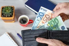 Male hands holding black leather wallet full of euro bills on gr. Male hands holding black leather wallet full of euro bills. Cup of coffee, notebook, pen and Stock Image