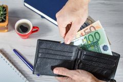 Male hands holding black leather wallet full of euro bills on gr. Male hands holding black leather wallet full of euro bills. Cup of coffee, notebook, pen and Royalty Free Stock Photo