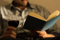 Male hands holding book. Close up of male hands holding book and glass of wine royalty free stock images