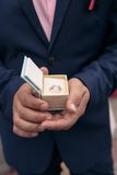 Male hands holding a box with a wedding ring. Male hands holding a box with a wedding golden ring Royalty Free Stock Photos