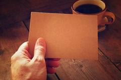 Male hands holding brown empty card over wooden table background and cup of coffee. retro style image, low key and warm tones.  Stock Photos