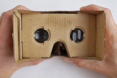 Male hands holding a cardboard goggles used for watching movies and playing games in virtual reality as a symbol of modern digital Royalty Free Stock Photos