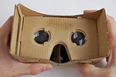 Male hands holding a cardboard goggles used for watching movies and playing games in virtual reality as a symbol of modern digital Royalty Free Stock Image