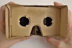 Male hands holding a cardboard goggles used for watching movies and playing games in virtual reality as a symbol of modern digital Royalty Free Stock Photography