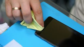 Male hands holding and cleaning a mobile phone screen to put on, apply a protective tempered glass to Protect a stock footage